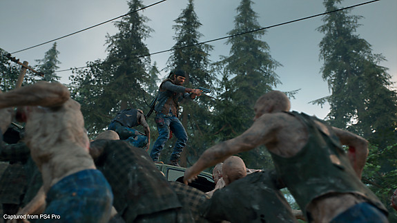 Days Gone - Deacon standing on a car surrounded by freakers