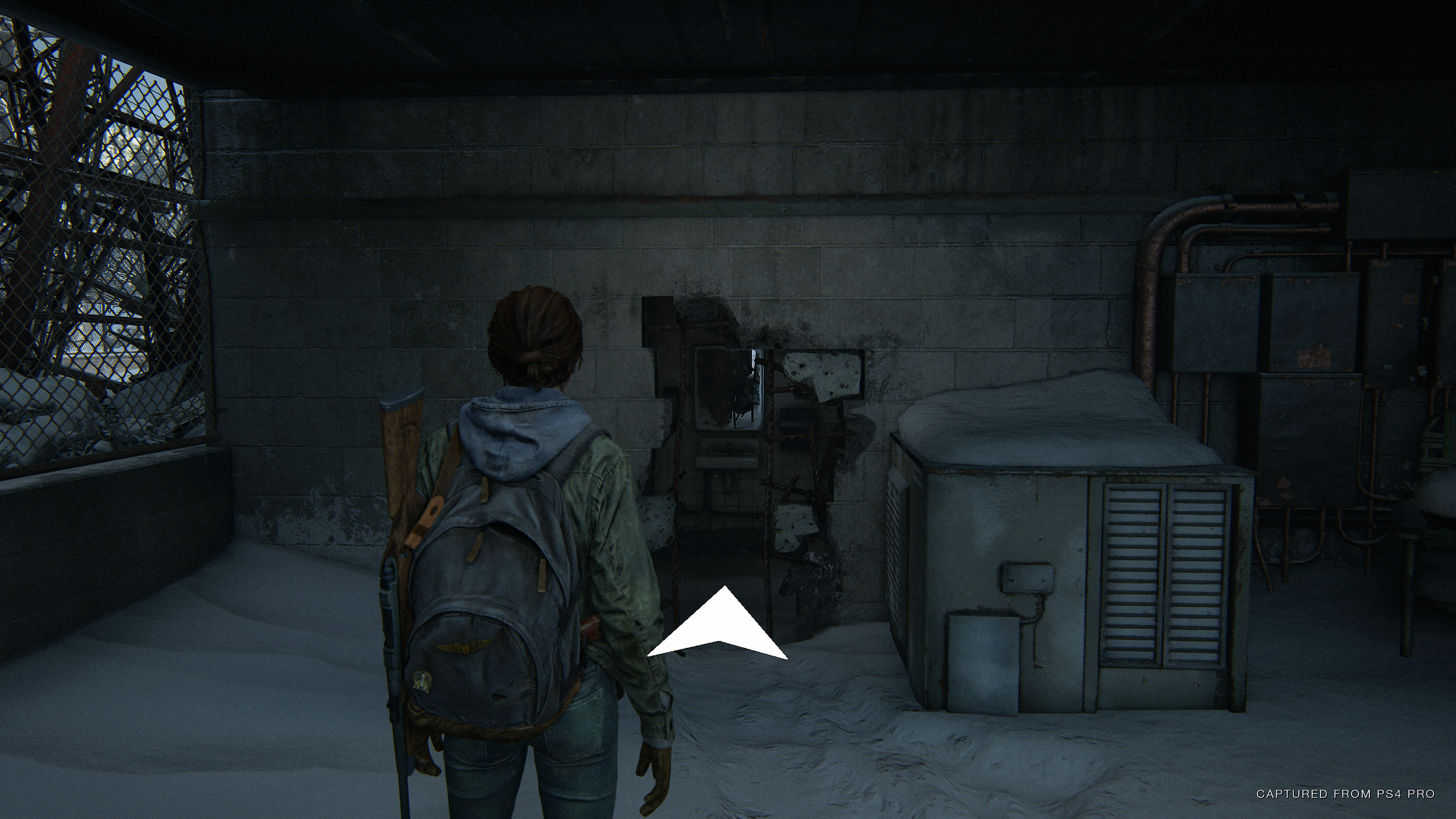 The player in front of a hole in the wall, with large arrow pointing towards it